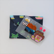 Navy and colourful pot plant fabric handmade earrings travel pouch, pictured closed with several colourful sets of earrings on storage board displayed.