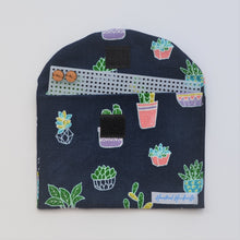 Navy and colourful pot plant fabric handmade earrings travel pouch, pictured open with timber studs on storage board displayed.