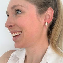 Hot cross bun stud earrings by Heartbeat Handicrafts being worn on model's ear