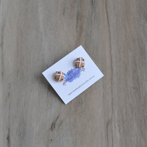Hot cross bun stud earrings shown on angled earrings card over timber flooring