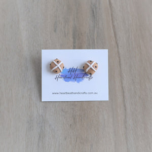 Hot cross bun stud earrings shown on earrings card over timber flooring
