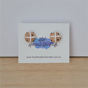 Hot cross bun stud earrings shown on earrings card on timber and white background