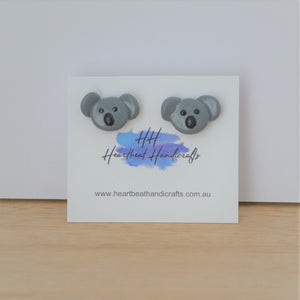 Koala stud earrings shown on earrings card on timber and white background
