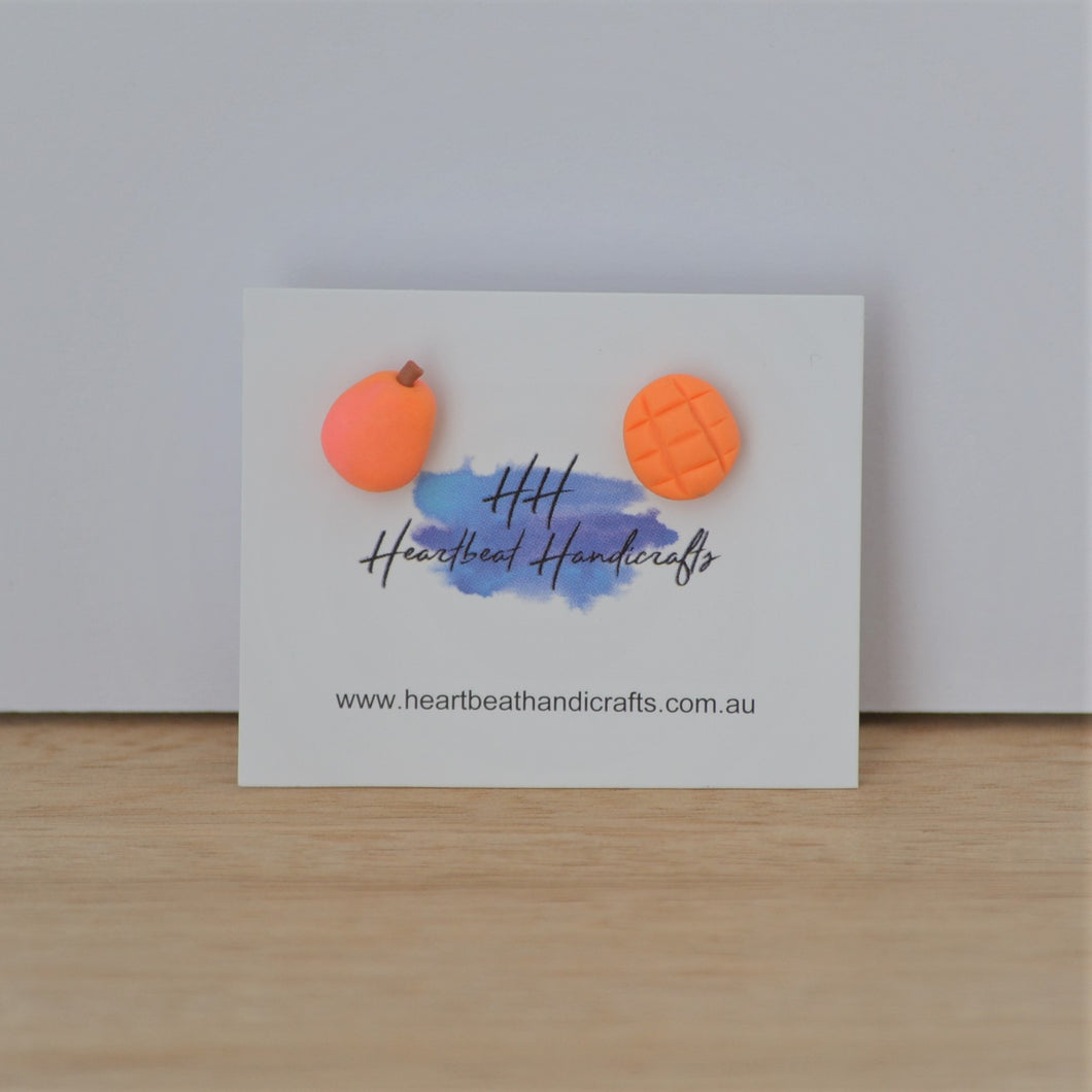 Mango stud earrings shown on earrings card on timber and white background