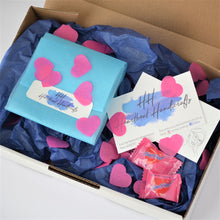 Packaging showing blue tissue paper, pink heart confetti and business card.