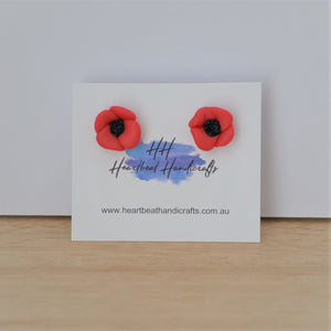 Poppy stud earrings shown on earrings card on timber and white background