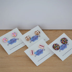 Group shot of donut earrings, hot cross bun earrings, iced vovo earrings and chocolate freckle earrings by Heartbeat Handicrafts, on timber background