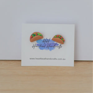 Taco stud earrings shown on earrings card on timber and white background