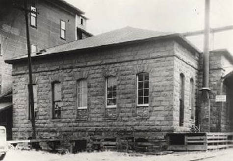 A black and white photo of the Dalles Mint. A one story building with 5 windows on 1 side.