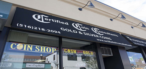 "Certified Coin Consultant's Storefront location in Rockville Centre, NY. It features a black banner with the company name, phone number, and website in white letters. There is a neon ""open"" sign and a ""Coins Gold"" Sign."