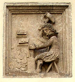 A Stone carving of a man hammering a coin at a work bench.