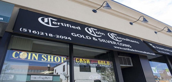 Certified Coin Consultant's storefront location. It features a black banner with the company logo, a phone number, and the website address. Also, there are two glass windows with two signs that read