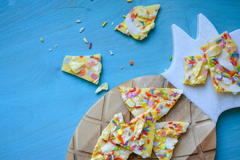 Tropical white chocolate bark with coconut and banana flavors, yellow color, and rainbow sprinkles
