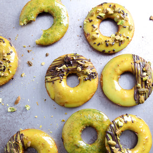 Vanilla Donuts with Pistachio flavored donut glaze and drizzled with dark chocolate and pistachio pieces