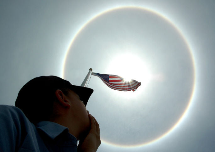 Man Looking Up a Flag Pole at an American Flag Which is Centered on a Solar Eclipse Halo