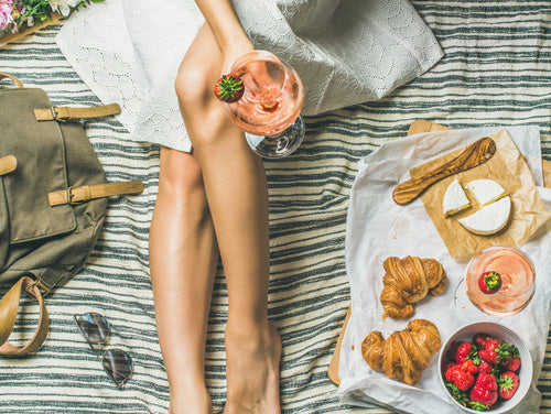 Legs and white skirt of woman on a picnic blanket with croissants and fruit. She holds a glass of JNSQ Rosé Cru wine.