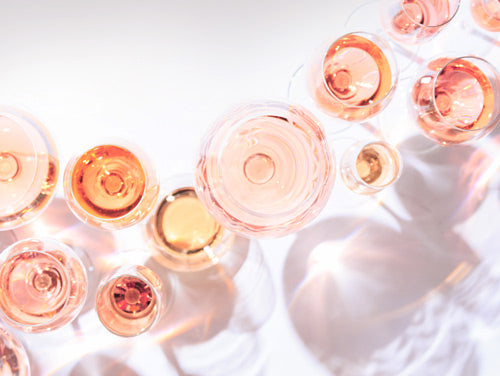 Several wine glasses on a white tabletop, all filled with JNSQ Rosé Cru wine.
