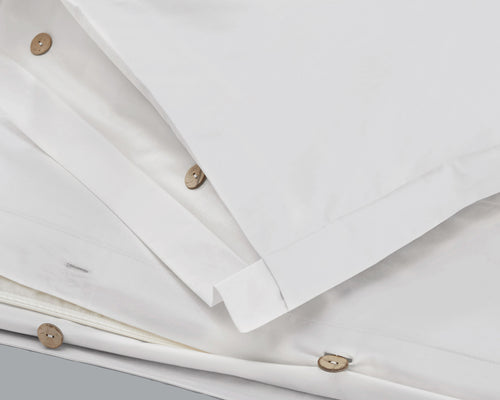 Closeup Of The Origanami Organic Cotton Percale Duvet Set, Color Cloud (True White), Featuring Sustainable Coconut Wood Buttons