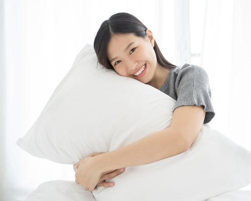 Young Woman Happily Hugging A Hulya Bamboo Adjustable Memory Foam Pillow