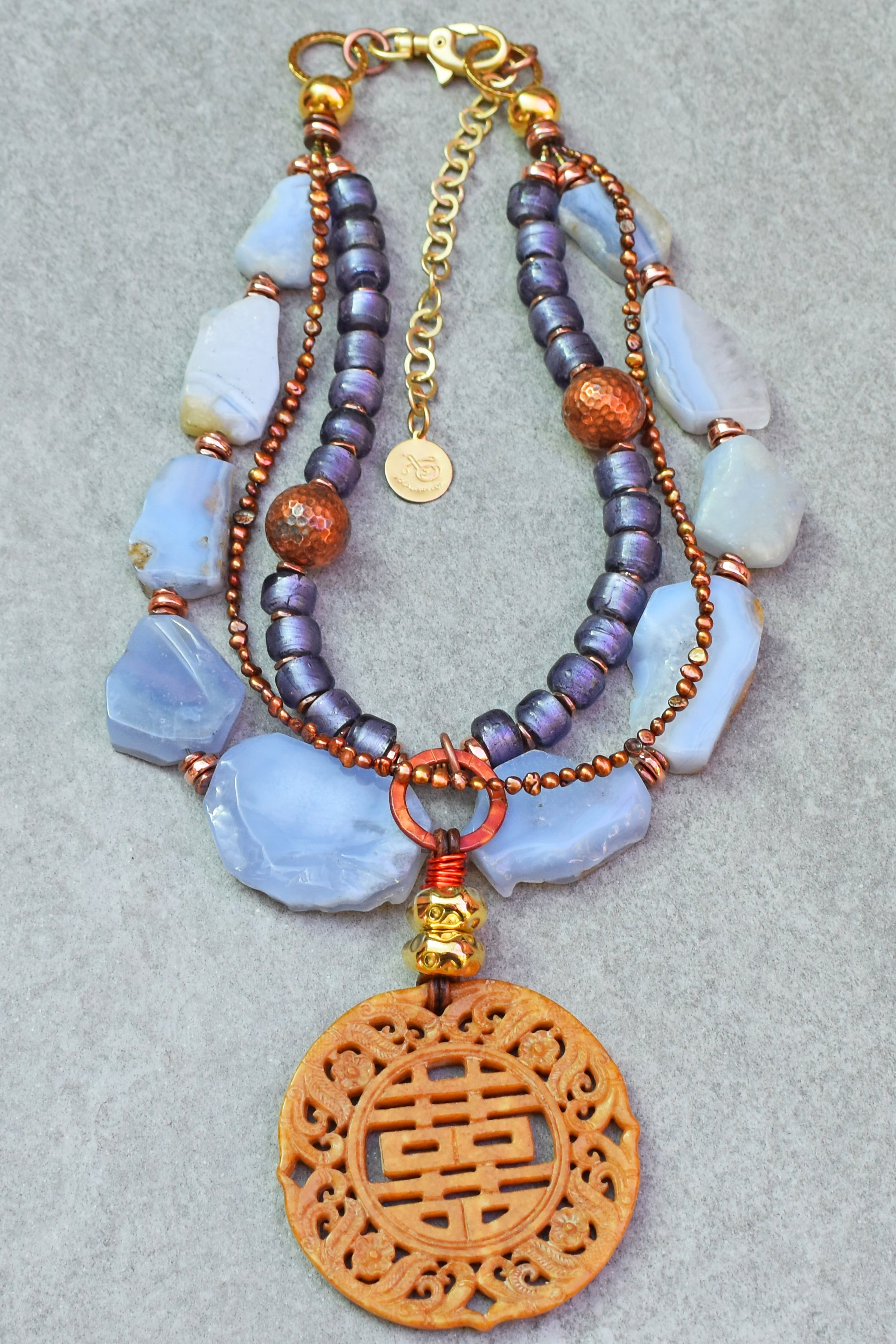 https://www.xogallery.com/collections/new/products/enchanting-blue-chalcedony-purple-copper-and-carved-jade-necklace