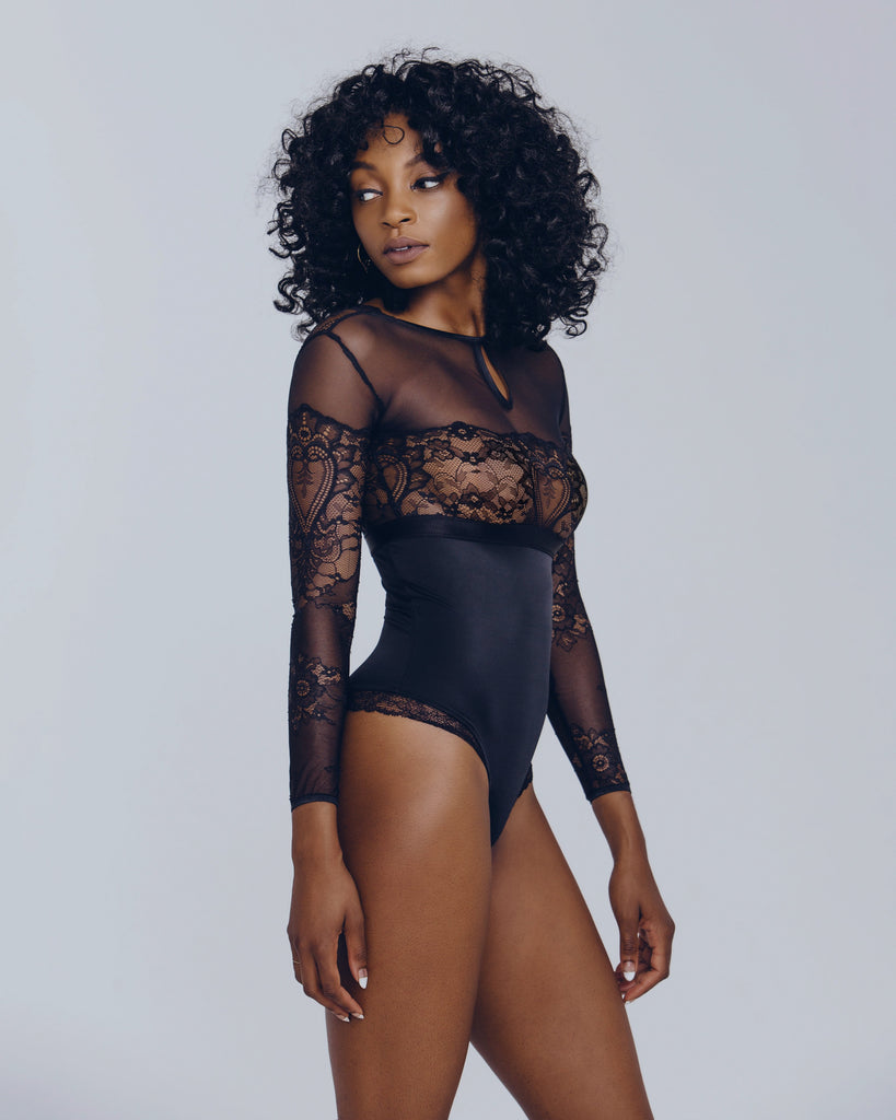 Long sleeved black bodysuit from Cadolle is sheer mesh and lace from the bust up with sleek microfiber at the bottom