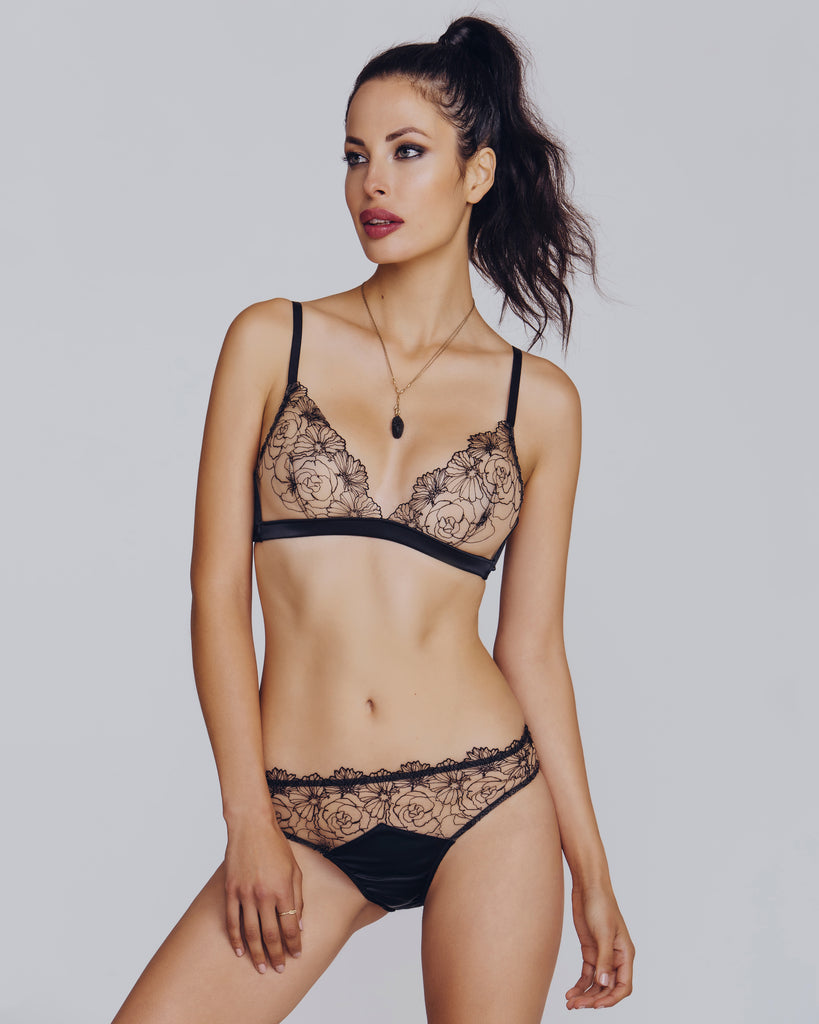 Classic bralette set  from Camille Roucher shows embroidered black flowers against a sheer beige mesh background
