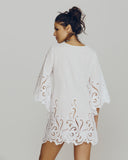 Dana Pisarra kaftan features scalloped edging at the v-neckline, bell sleeves, and mid-thigh hemline