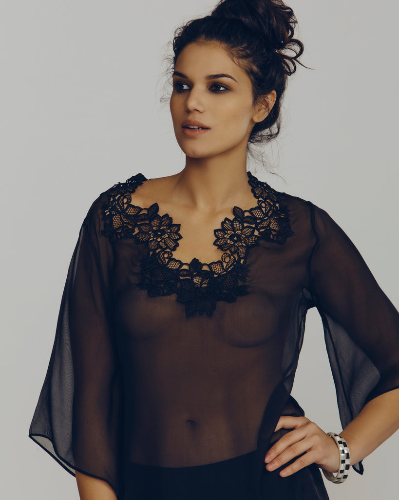 Sheer black silk top has 3/4 bell sleeves and a v neckline
