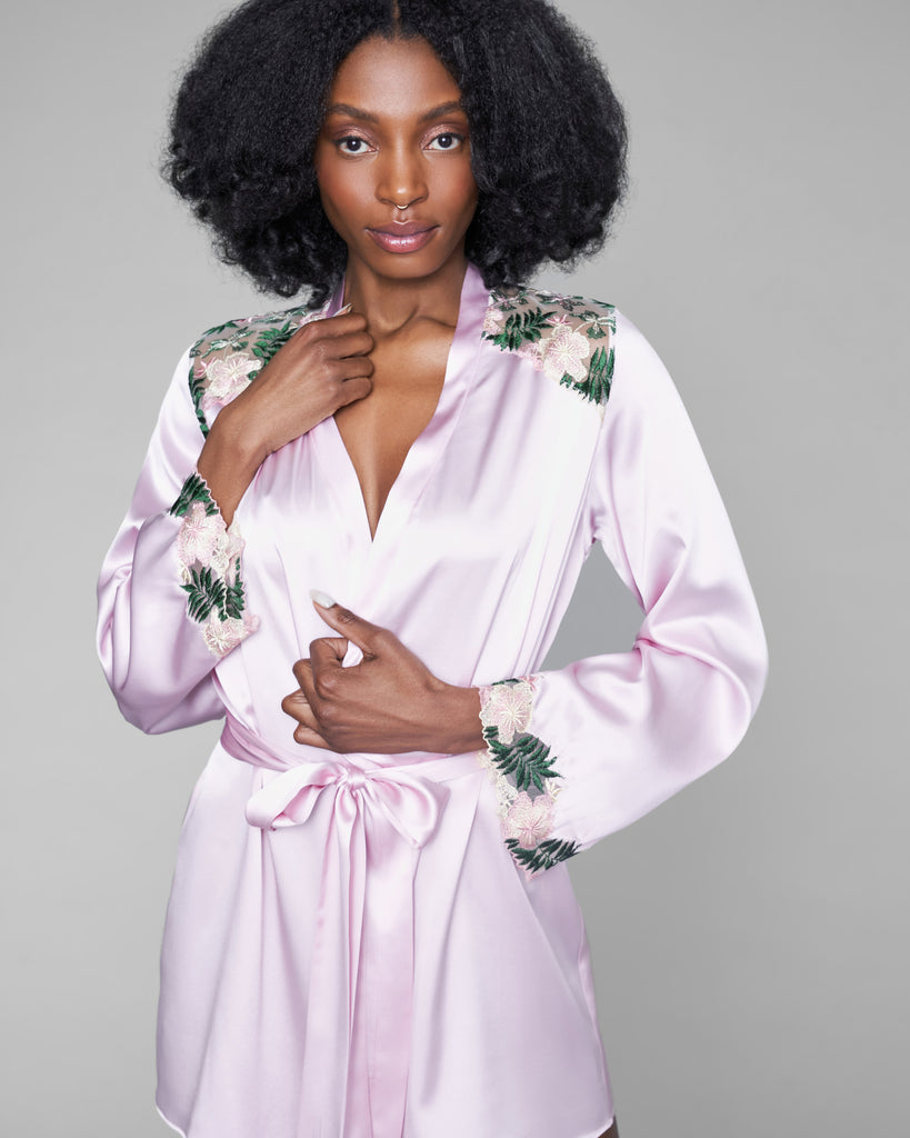 Classic robe from Gilda & Pearl is crafted from pale pink silk accented with pink and green floral embroidery