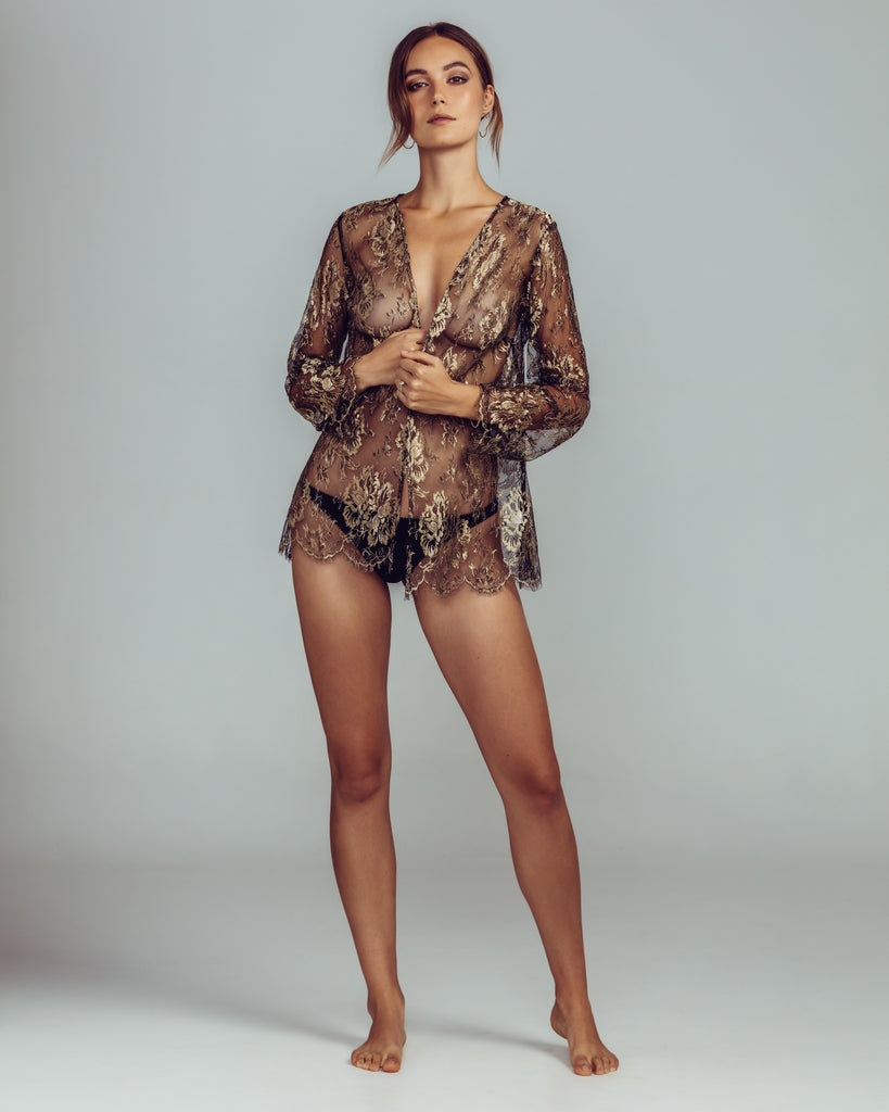 Sheer black and gold lace Melitza jacket from Gilda & Pearl has scalloped eyelash detailing at the sleeves and hem