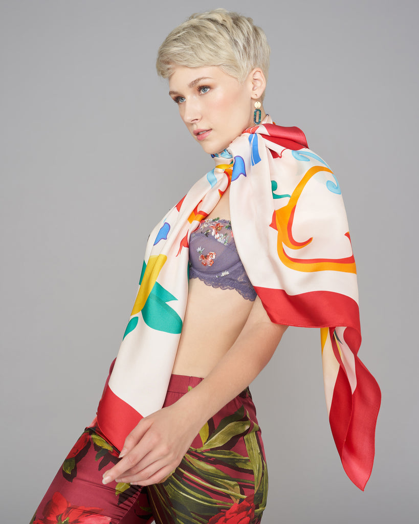 Ika Paris Dolce square scarf features an abstract print on a cream background in shades of red, green, yellow, blue and orange