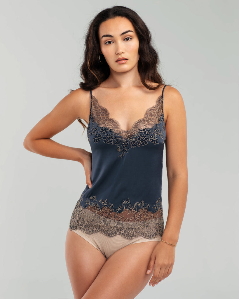 The V neckline of Merle Noir's Maya Blue silk camisole is created with swaths of sheer floral lace, with the pattern appliquéd to continue into the bust and the backing silk cut to match the design of the lace