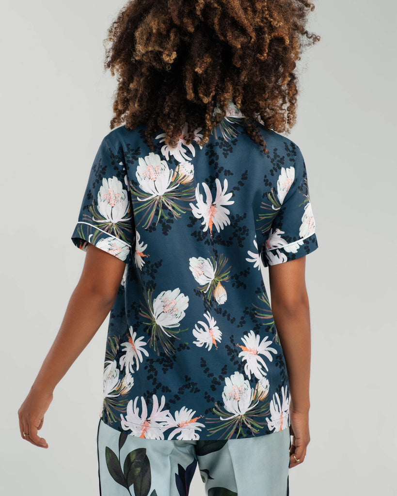 Navy blue Queen of the Night camp shirt from Violet and Wren is a lightweight silk/cotton blend patterned with hand painted cactus flowers in shades of white, pink and green