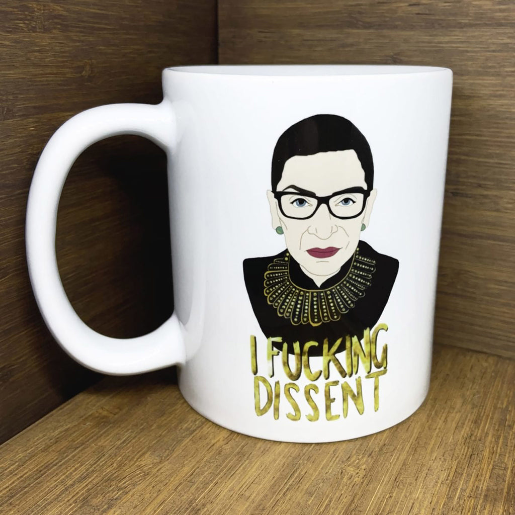 "white ceramic mug with illustration of ruth bader ginsburg and the words ""I fucking dissent"""