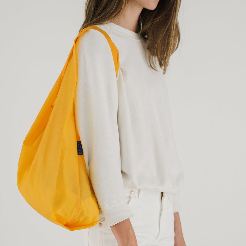 baggu reusable standard ripstop nylon bag in yolk yellow on shoulder