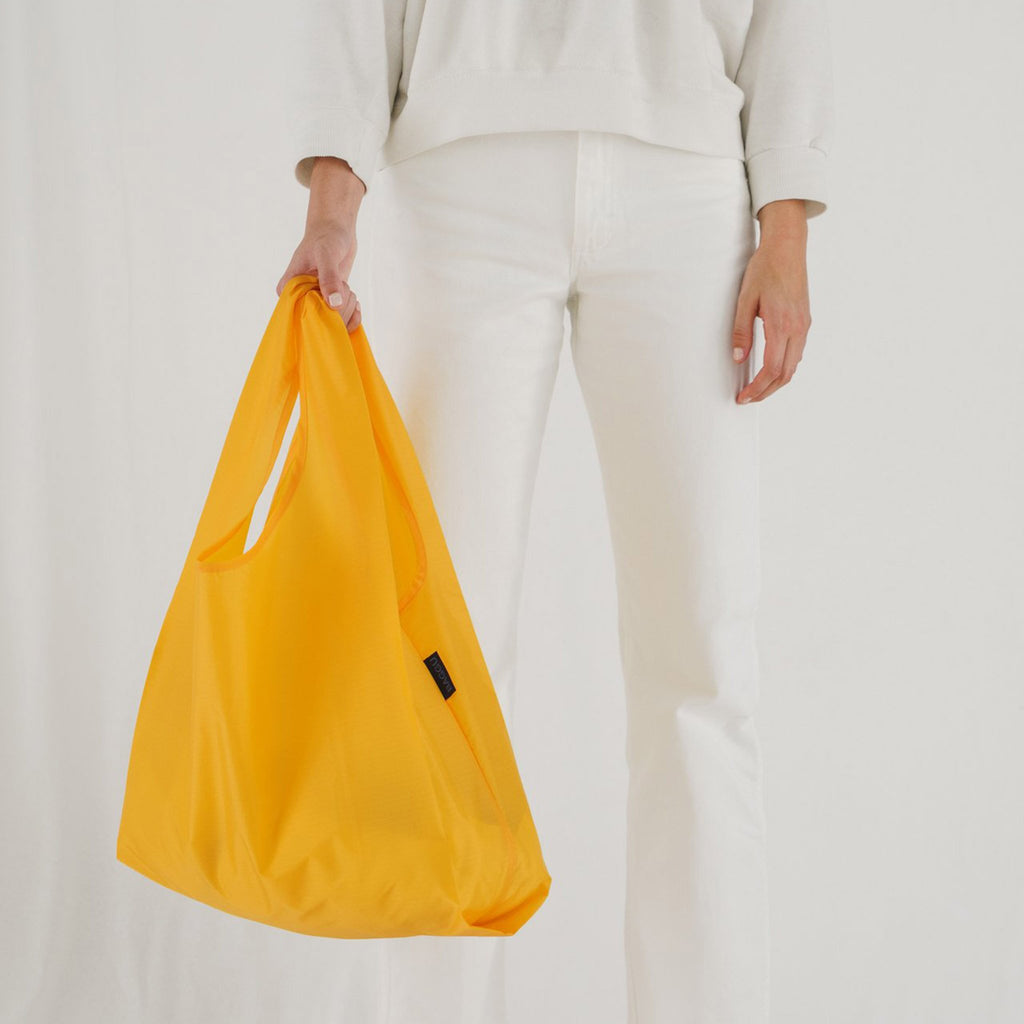 baggu reusable standard ripstop nylon bag in yolk yellow with woman carrying