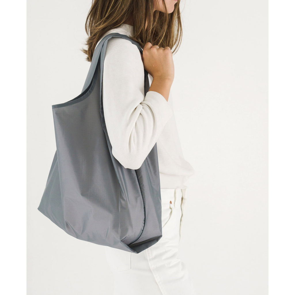 baggu standard ripstop nylon reusable shopping bag grey on shoulder
