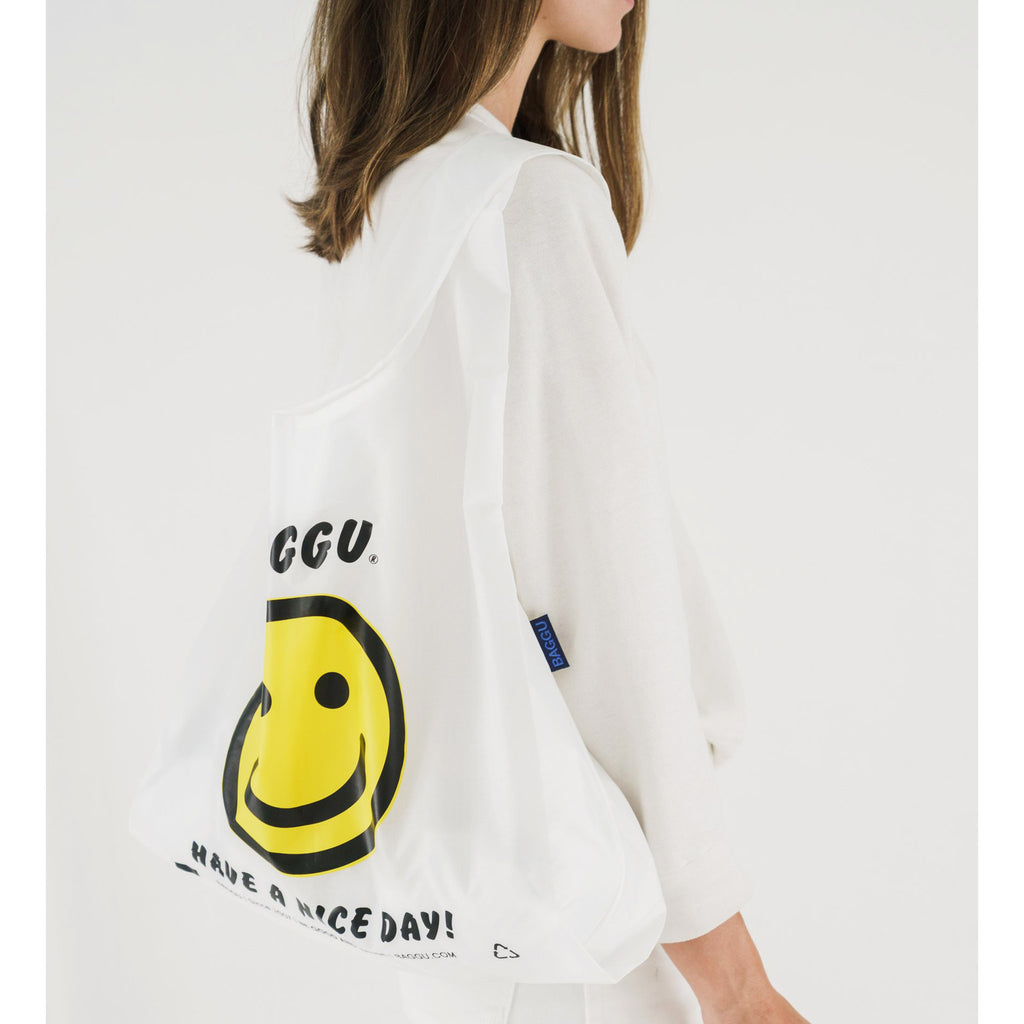 baggu reusable standard white ripstop nylon bag in thank you happy with yellow smiley face and have a nice day in black text on shoulder