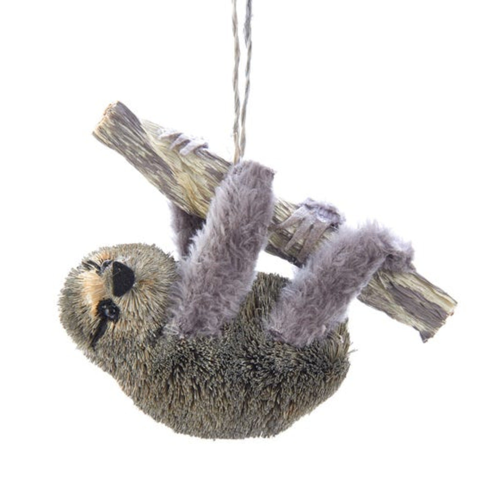 sloth ornament made from buri palm and faux fur hanging on a wood branch