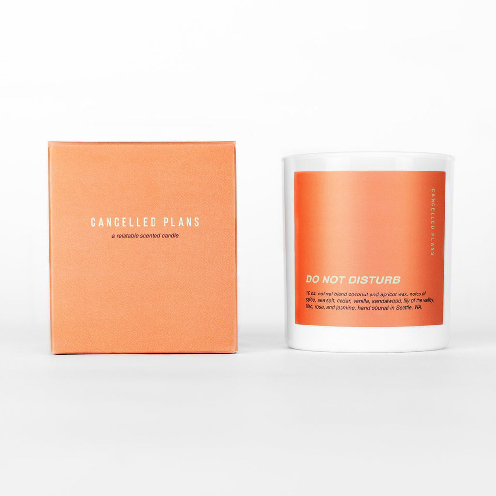 cancelled plans do not disturb scented coconut apricot wax candle in white glass tumbler with orange colored label and box