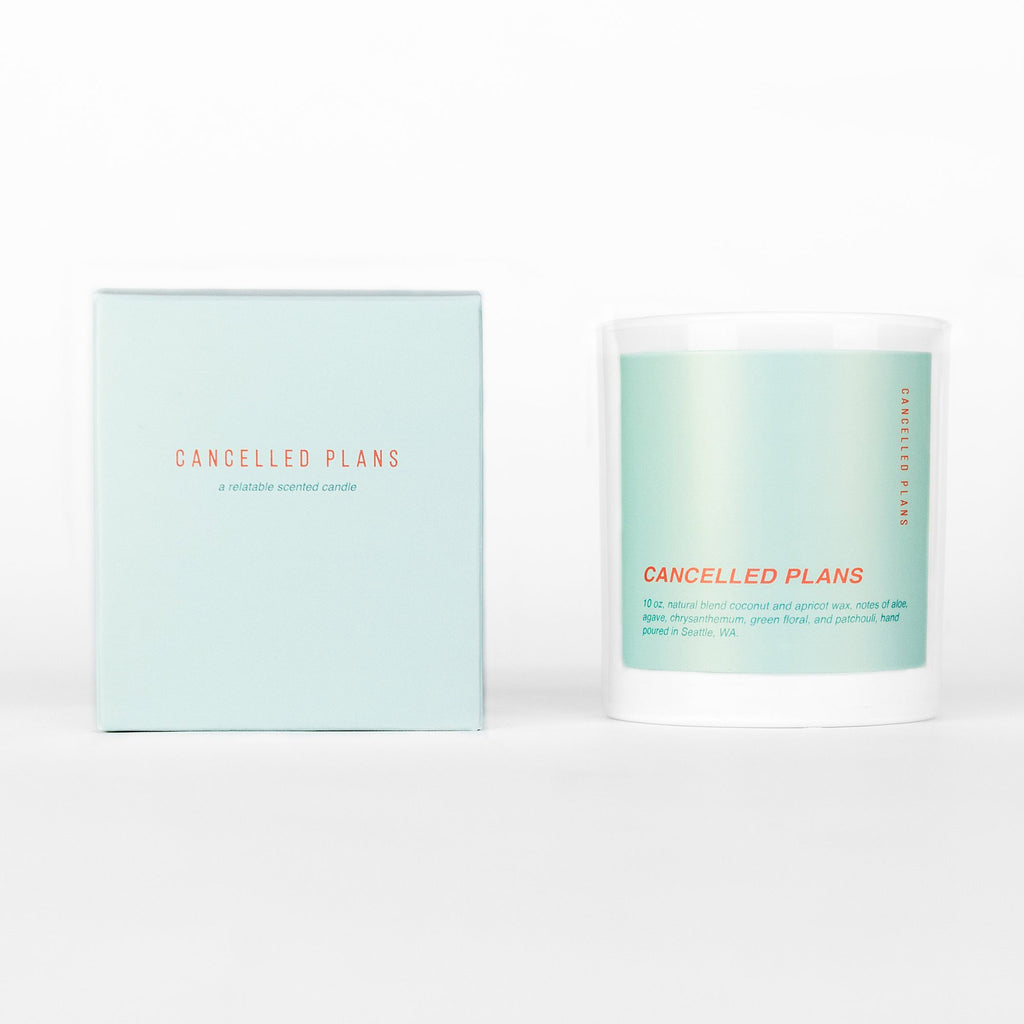 cancelled plans scented coconut apricot wax candle in white glass tumbler with light aqua colored label and box