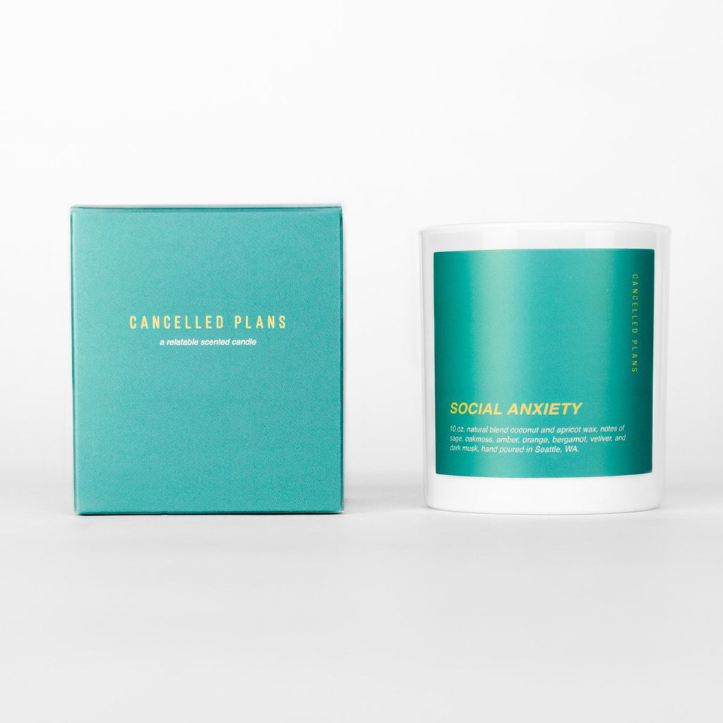 cancelled plans social anxiety scented coconut apricot wax candle in white glass tumbler with teal colored label and box