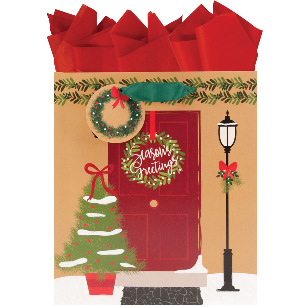 medium gold gift bag featuring a door with wreath, christmas tree and garland decoration