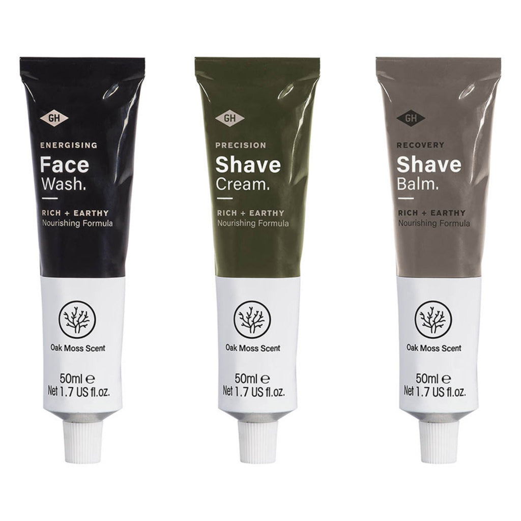 black and white tube of face wash, green and white tube of shave cream, and grey and white tube of shave balm