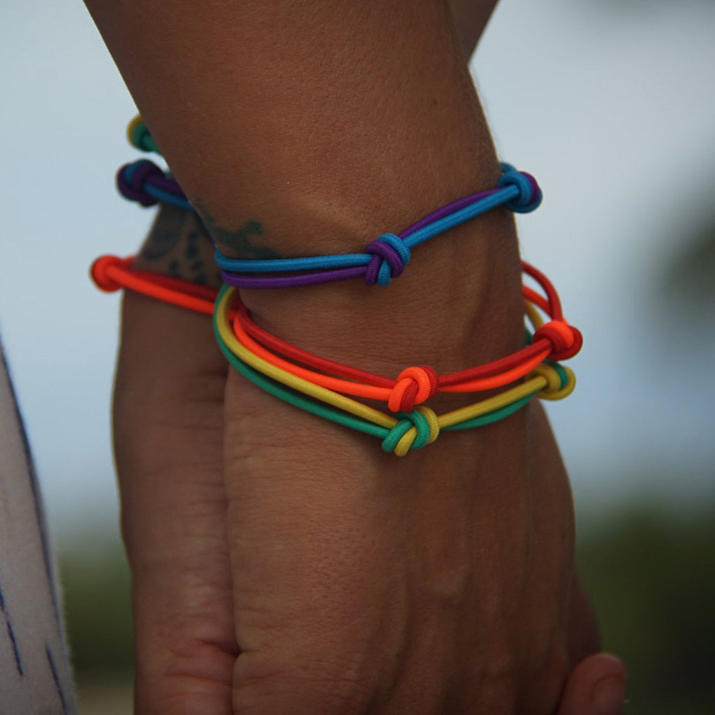 colors for good love is love pride bracelet set of three on wrists
