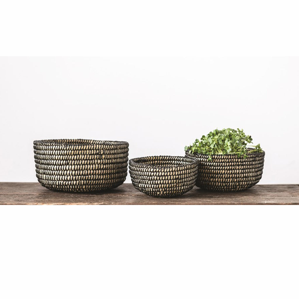creative coop set of three natural hand woven grass baskets with black binding with greenery