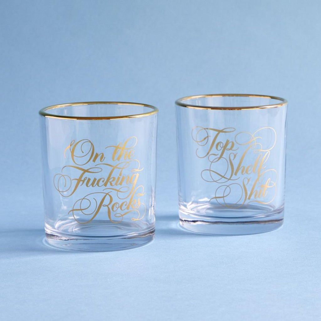 "set of 2 clear rocks glasses with gold rims and gold script reading ""on the fucking rocks"" and ""top shelf shit"""