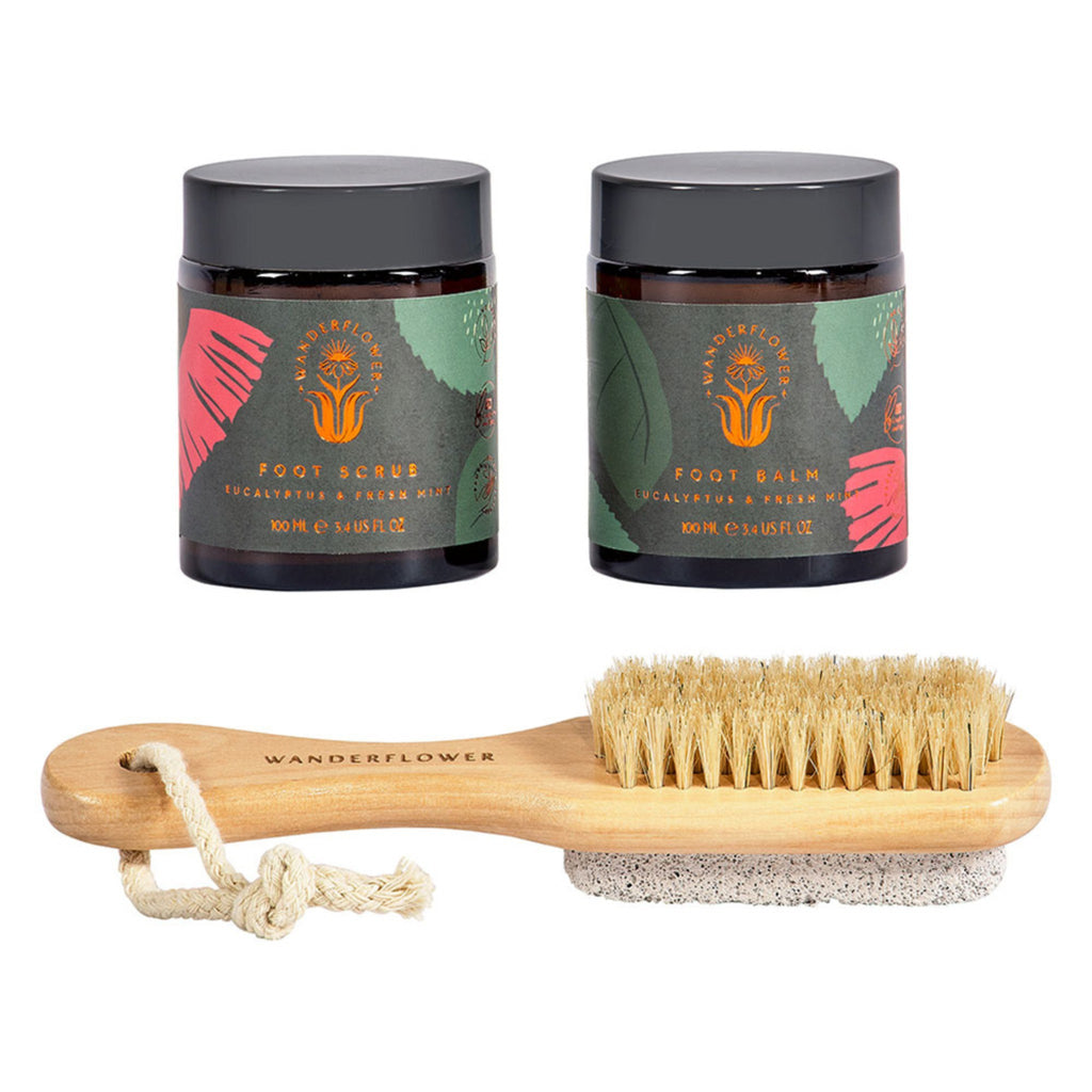 foot scrub and foot lotion in amber glass jars with wooden scrub brush with pumice stone