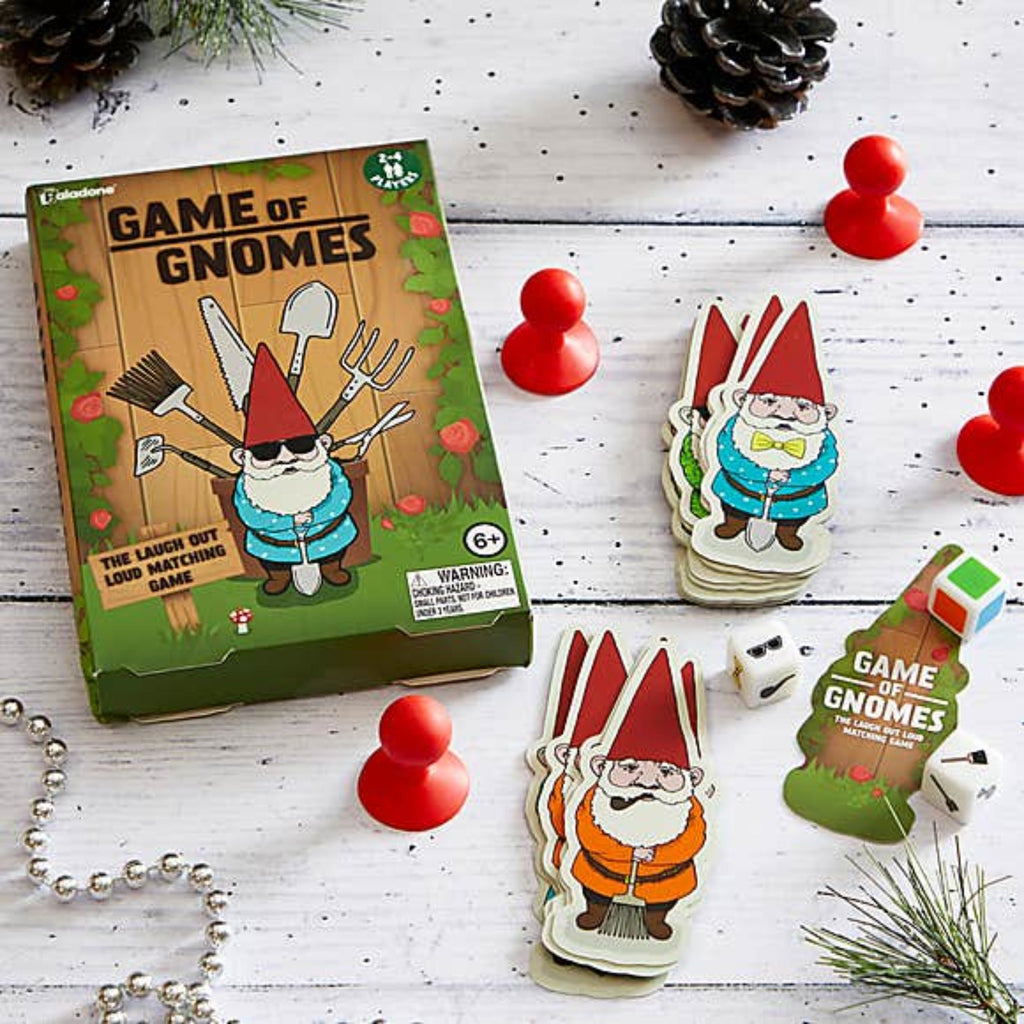 game of gnomes box with illustration of a gnome on a throne made of garden tools, red game pieces, dice, and gnome shaped cards