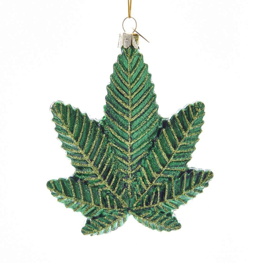 glass christmas ornament in the shape of a green cannabis leaf with gold glitter accents